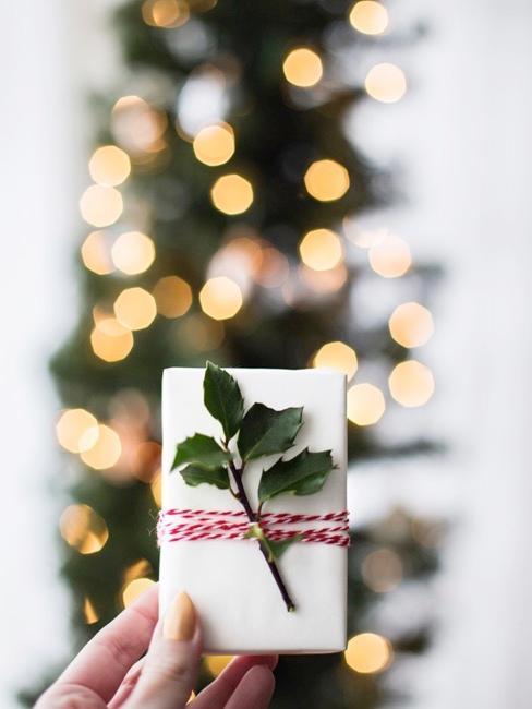Hand die een secret santa cadeau voor een kerstboom houdt.