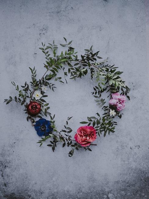 Una bella corona di fiori coloratissima su sfondo grigio