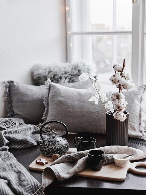 Pianta di cotone in vaso nero vicino a vassoio con teiera e tazzine