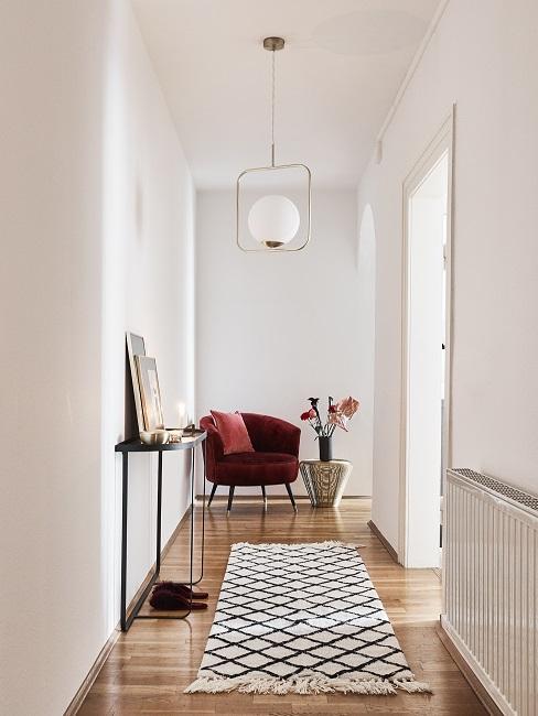 Schmalen Flur gestalten mit Sessel, Konsole, Teppich und Pflanze