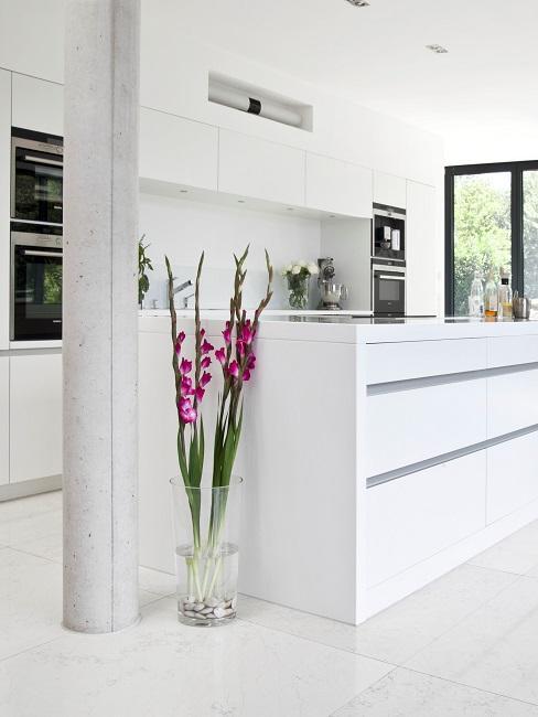Weiße Küche mit Kochinsel, integrierten Küchengeräten und Pflanzen Deko zu einem weißen Naturstein Boden