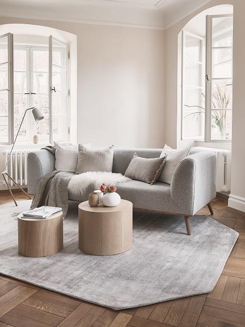 Helles Beige als Wandfarbe in Wohnzimmer mit hellgrauem Sofa, Teppich und Couchtischen aus Holz