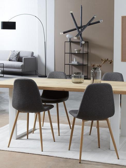 Modernes Esszimmer mit beigefarbener Wand, schwarzen Stühlen, Pendelleuchte und hellem Holztisch