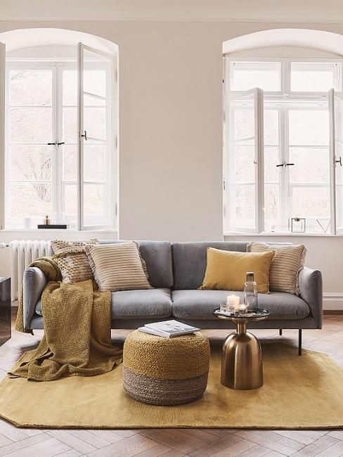 Wandfarbe Beige mit grauem Sofa und gelben Textilien