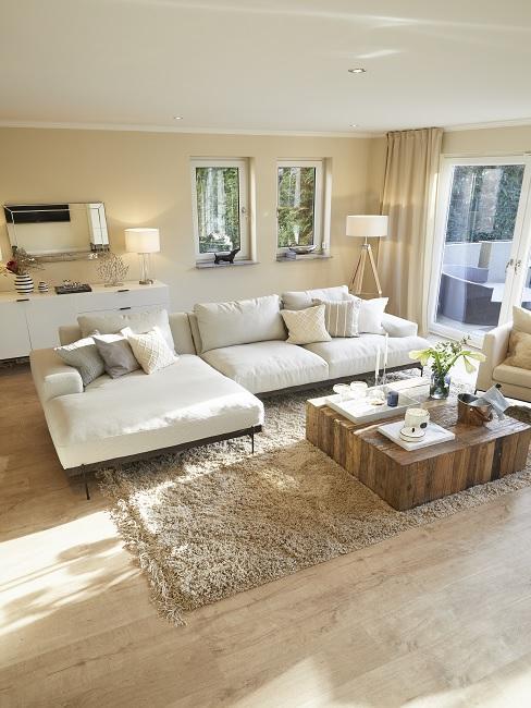 Sandfarbenes Wohnzimmer mit cremefarbenen Sofa, braunen Teppich und Couchtisch aus Massivholz
