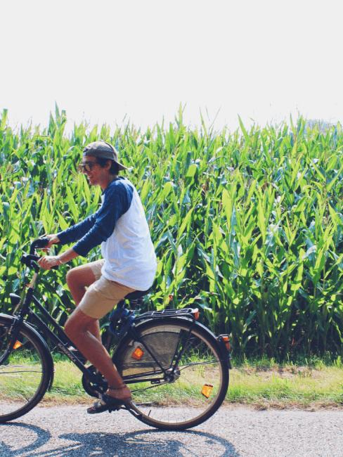 chico montando en una bici con maiz de fondo
