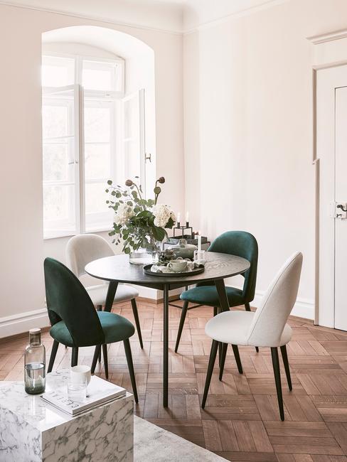 Petit coin salle à manger avec table en marbre blanc, deux chaisses blanches et deux chaises vertes dans un appartement ancien