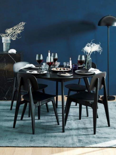 sala da pranzo con tavolo nero e parete blu