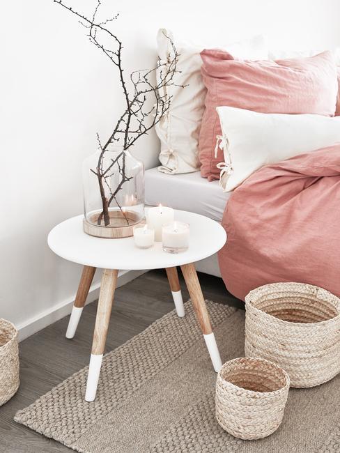 Drewinany nocny stolik z wazone z gałęźmi, plecione kosze i łózko