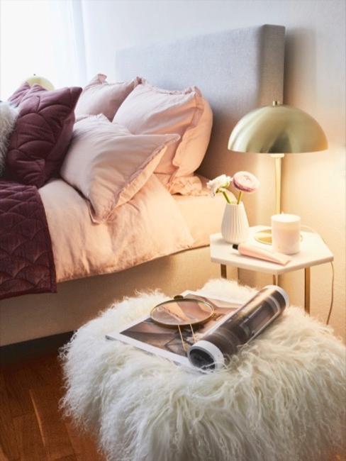 Sgabello in pelliccia sintetica bianca davanti al letto rosa e al comodino leggero