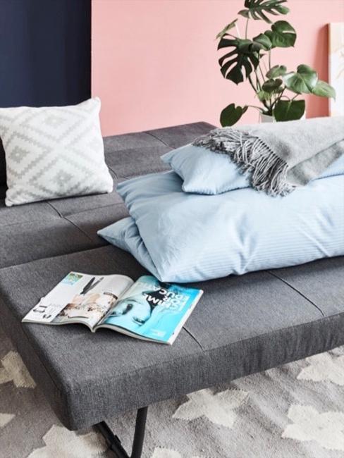 Rozłożona szara sofa futon udekorowana kocem, poduszkami i magazynem.