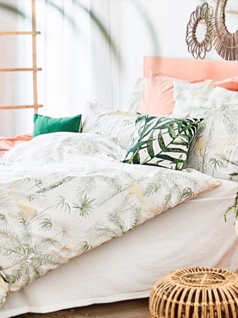 Pastelowo-morelowe łóżko z pościelą z motywem dżungli i drewnianym stolikiem nocnym oraz rattanowym taboretem