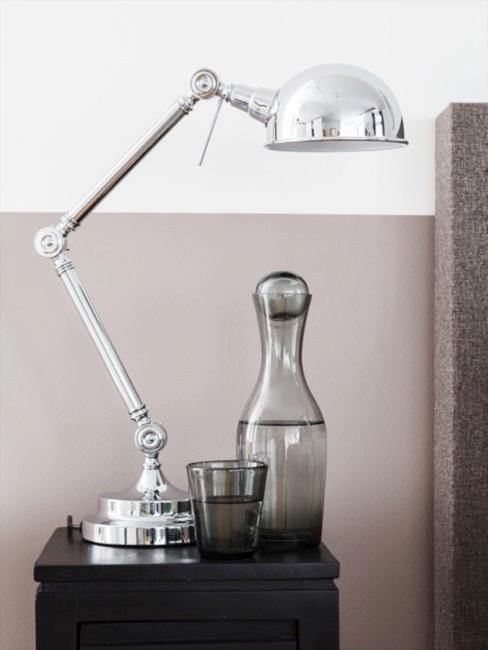 Szklanka i karafka z przydymionego szkła na czarnym drewnianym stoliku nocnym z srebrną lampą stołową