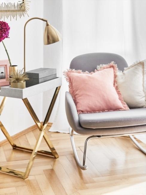 Przytulny kąt z jasnoszarym, skórzanym stołem bocznym i złotą ramą obok jasnoszarego fotela bujanego ozdobionego różowymi poduszkami