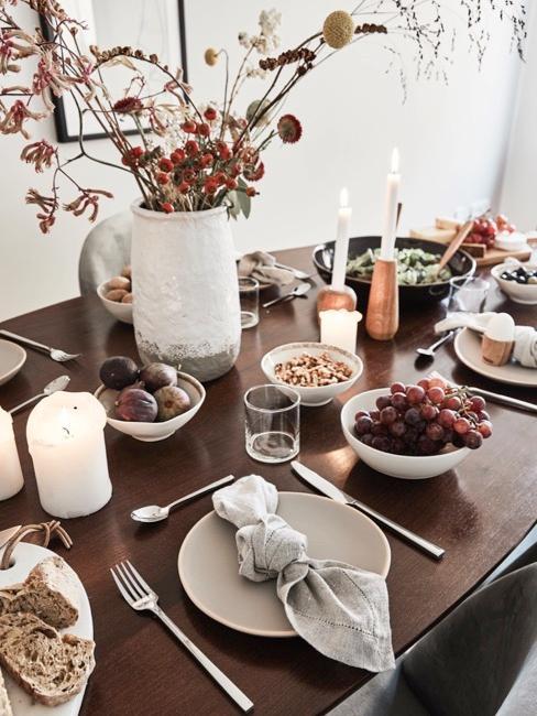 tavola in legno scuro apparecchiata senza tovaglia con piatti bianchi e vaso di fiori