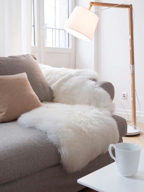 Zbliżenie szarej kanapy z jasną imitacją skóry jagnięcej.