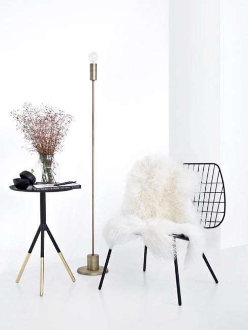Miejsce do siedzenia z jagnięcą skórą na krześle obok stojącej lampy i niewielkiego stolika
