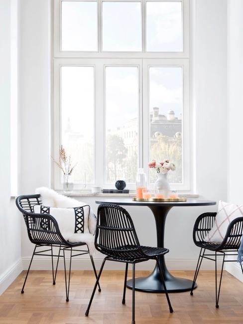 Zona pranzo con tavolo e sedie nere e ampie finestre