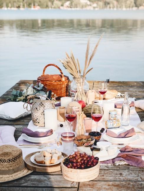 picnic en la orilla del lago, con una cesta de picnic, fritas, copas de vino tinto y decoración
