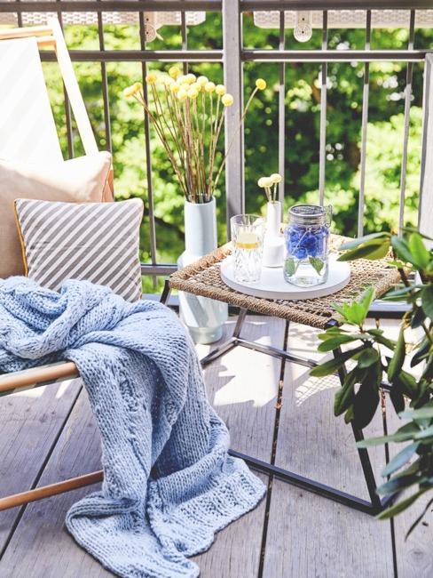 Blacón decorado con una mesa y una silla con una manta de punto azul