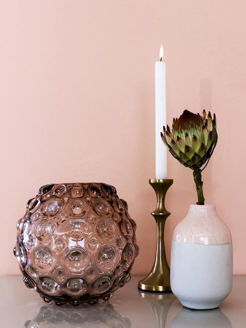 Półka z kamionkowym wazonem i innymi dekoracjami.