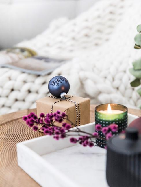 un regalo navideño decorado con una bola navideña, bandeja de mármol blanco con una vela y unas plantas