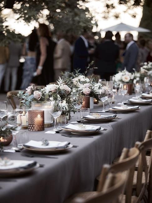 Blumen Tischdeko mit weißen Rosen und Kerzen und gedecktem Tisch