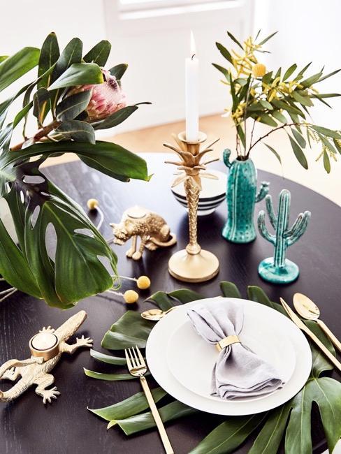Table de salle à manger avec vase cactus et une assiette avec couverts dorés, et les grandes feuilles vertes comme décoration
