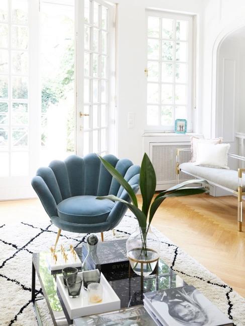 Jasny salon z turkusowym fotelem oraz dywanem