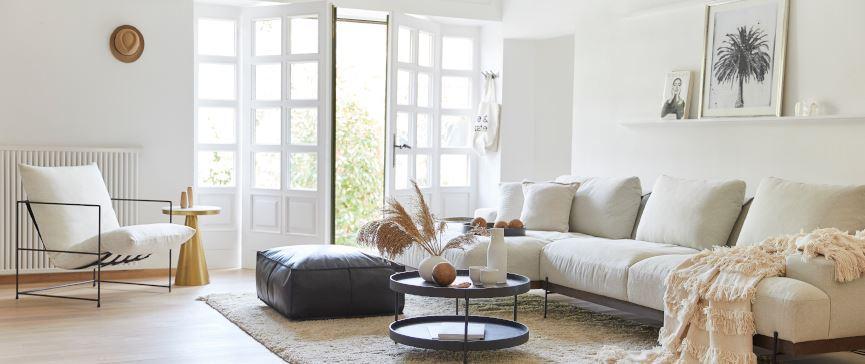 Jasny i przestronny salon z dużą kanapą oraz fotelem z konstrastującą ciemną, skórzaną pufą