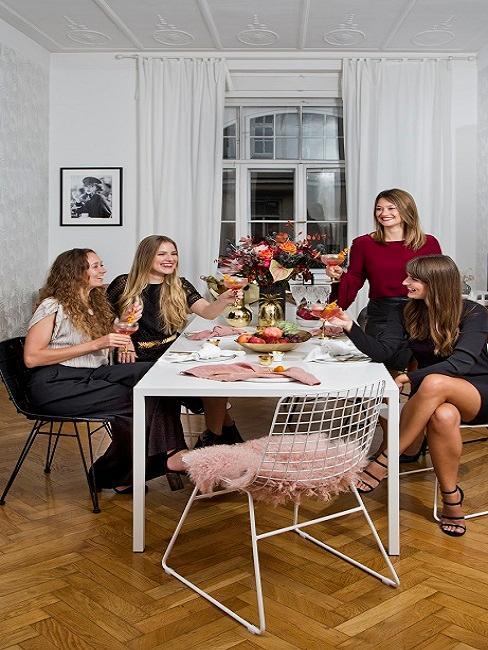 Cztery kobiety zgromadzone wokół stołu, świętujące wieczór panieński
