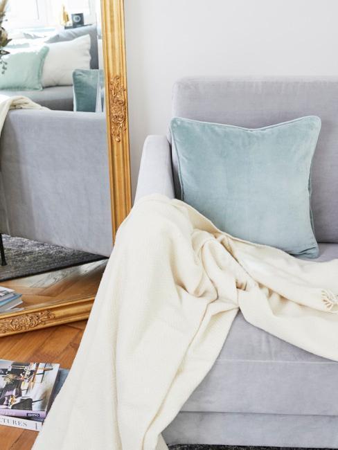 Nahaufnahme graue Westwing Samtcouch mit blauem Samtkissen neben goldenem Standspiegel
