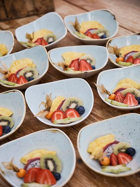 Owoce w małych miseczkach na drewnianej tacy