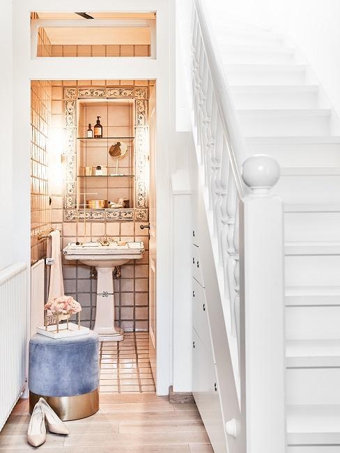 Der Eingang zu einem kleinen Bad neben einer großen Treppe, davor ein Pouf und High Heels