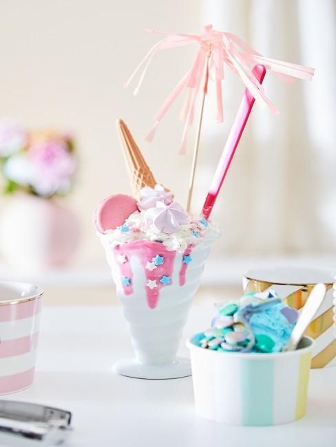 Eis mit rosa Soße in einem Becher und rosa Deko-Schirmchen