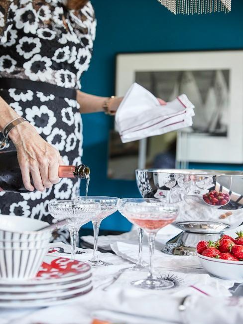 Frau schenkt Champagner in Champagner Schalen auf Esstisch
