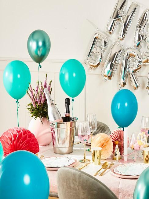 Ballons de différents tons de turquoise attachés à la table de fête