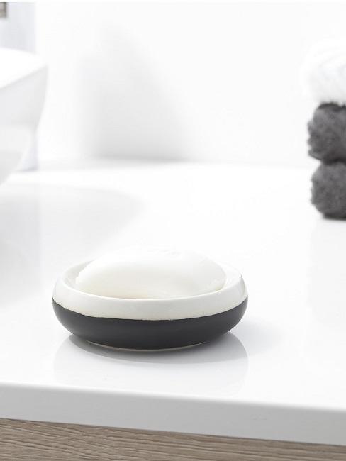 Seifenschale mit Seife auf dem Waschtisch neben dem Waschbecken und Handtüchern