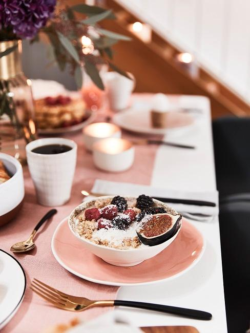 Schüssel mit Müsli auf dem gedeckten Tisch auf einem Teller