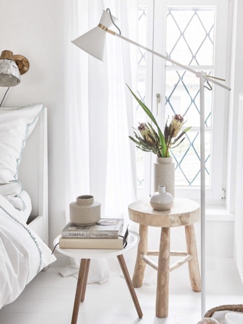 Stołek jako szafka nocna w jasnej sypialni z biała lampa podłogową