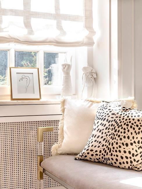 Sofa przy oknie z poduszkami dekoracyjnymi w panterkę