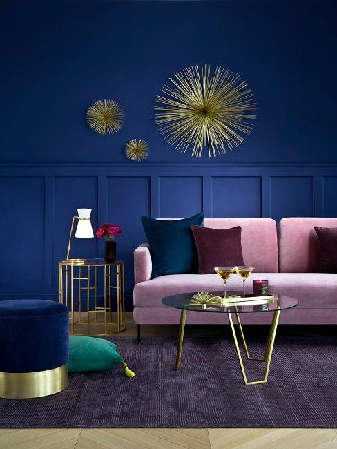 Różowa sofa z różnokolorowymi poduszkami, na ścianie złote dekoracje