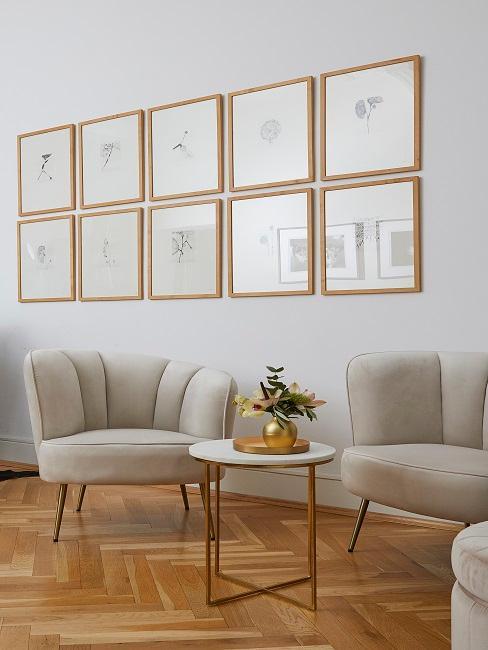 Zwei Sessel in Samt neben einem kleinen Beistelltisch unter einer dekorativen Bilderwand