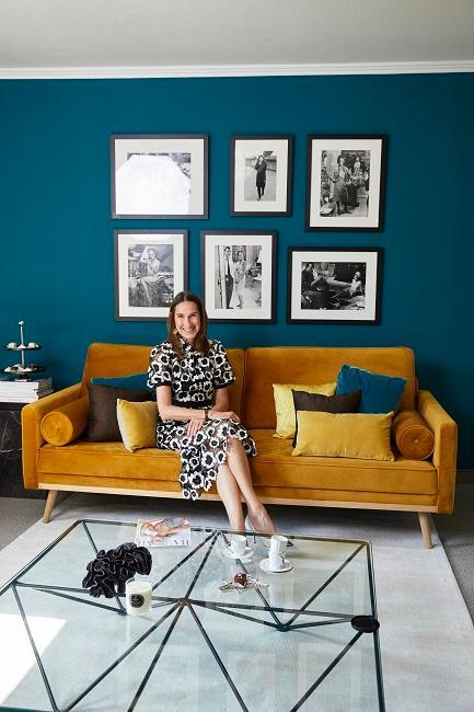 Anette Weber sitzt in ihrem Design-Wohnzimmer auf dem Sofa in Gelb