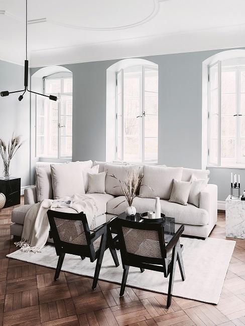 Design-Wohnzimmer in einer Altbauwohnung mit einem beigen Sofa und zwei Stühlen mit Wiener Geflecht