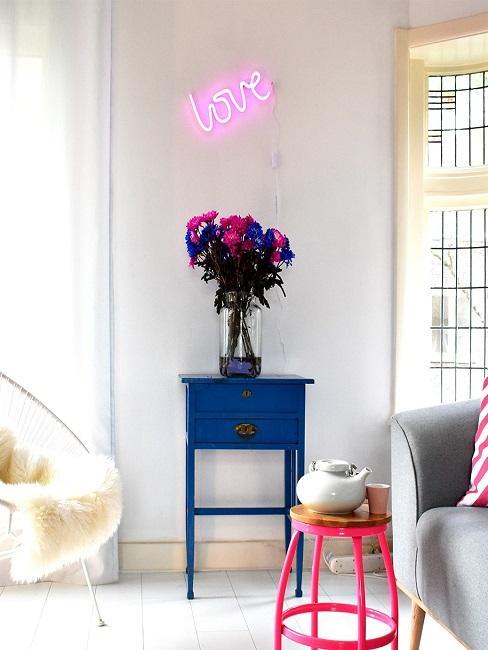 """Neon-Leuchtschrift in Pink an der Wand im Wohnraum mit dem Wort """"Love""""."""