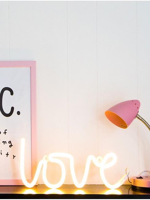 """Neon Leuchtschrift auf dem Schreibtisch mit dem Wort """"Love""""."""
