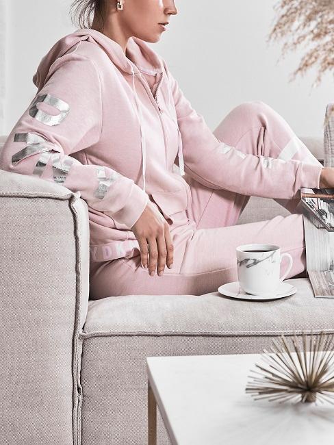 Eine Frau sitzt in Ihrem Wohnzimmer gemütlich auf der Couch und relaxt in einem Baumwoll-Trainingsanzug.