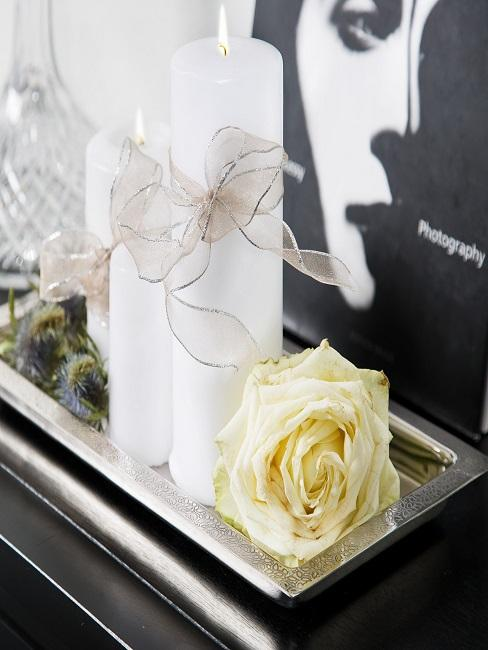 Kommode dekorieren mit weißen Kerzen und Rose