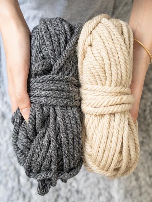 Frauenhände halten zwei Wollknäule, einer davon in Wollweiß, der andere in Grau